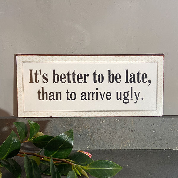 Plåtskylt-med-text,-it's-better-to-be-late-than-to-arrive-ugly