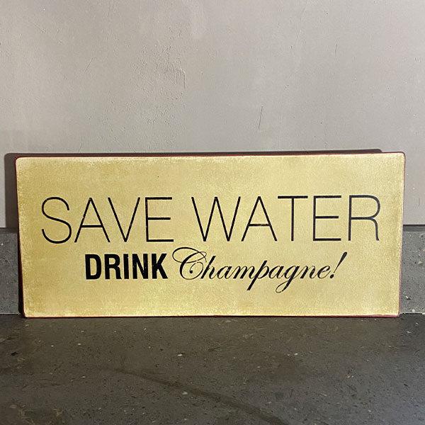 Plåtskylt-med-text,-save-water-drink-champagne
