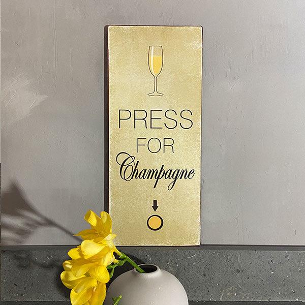 Plåtskylt-med-text,-press-for-champagne