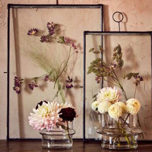 Ram av glas och svart metall med blommor i