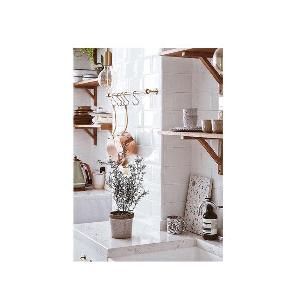 Kort på ett kök med en vacker växt och köksredskap