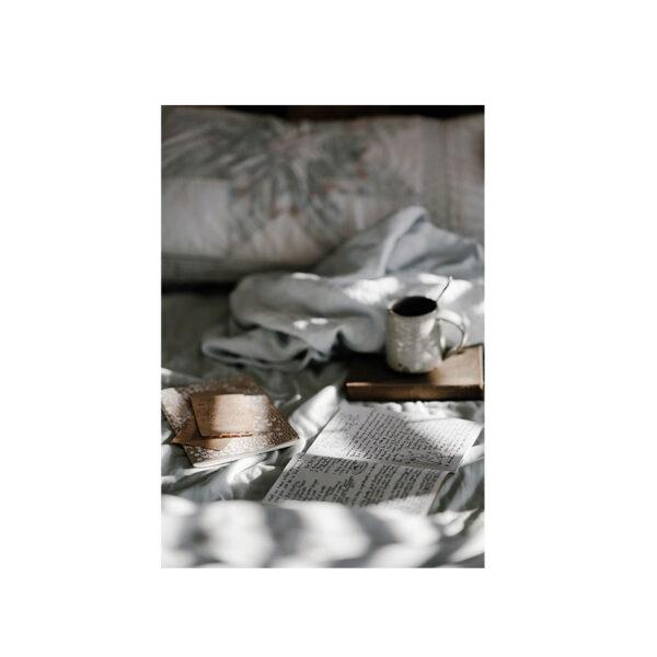 Kort med morgonljus, kaffekopp vid en säng